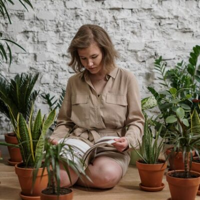 woman-sitting-while-reading-book-near-potted-plants